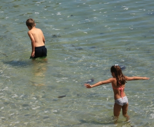 Two kids enjoying the water in very different ways.